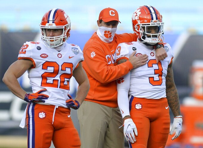 Clemson head coach Dabo Swinney, center, hugs wide receiver Amari Rodgers, right, during warm-ups before the Atlantic Coast Conference championship NCAA college football game against Notre Dame, Saturday, Dec. 19, 2020, in Charlotte, N.C. (Jeff Siner/The News & Observer via AP)