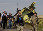 FILE In this file photo taken on Tuesday, July 22, 2014, A pro-Russian rebel holds a gun passing by plane wreckage as members of the OSCE mission to Ukrainearrive for a media briefing at the crash site of Malaysia Airlines Flight 17, near the village of Hrabove, eastern Ukraine. International investigators on Wednesday, June 19, 2019 announced murder charges against three Russians, including a prominent separatist rebel commander, and one Ukrainian, for their alleged roles in blowing a Malaysia Airlines passenger jet out of the sky five years ago, a shocking attack that killed all 298 people on board. (AP Photo/Vadim Ghirda, File)