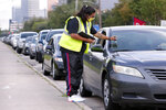 Volunteer Sharely Gomez marks the windshield after taking information from clients in their cars as they wait in line in before the food distribution begins at the West Houston Assistance Ministries Wednesday, Oct. 14, 2020, in Houston. Each car is marked to denote if there are kids or pets, gluten allergies and other special hygiene needs. WHAM is one of the many distribution points that gets food from the Houston Food Bank and other retail contributors to those in need around the 18 counties served by the food bank. (AP Photo/Michael Wyke)