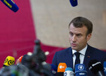 French President Emmanuel Macron speaks with the media as he arrives for an EU summit at the Europa building in Brussels, Thursday, Oct. 17, 2019. Britain and the European Union reached a new tentative Brexit deal on Thursday, hoping to finally escape the acrimony, divisions and frustration of their three-year divorce battle. (AP Photo/Virginia Mayo)