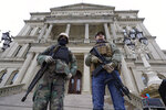 Armed men stand on the steps at the State Capitol after a rally in support of President Donald Trump in Lansing, Mich., Wednesday, Jan. 6, 2021. (AP Photo/Paul Sancya)