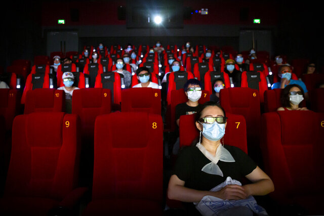 People wearing face masks to protect against the coronavirus sit spaced apart as they watch the film