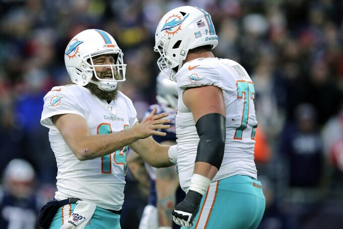 Miami Dolphins quarterback Ryan Fitzpatrick celebrates his winning touchdown pass to Mike Gesicki with guard Jesse Davis, right, in the second half of an NFL football game against the New England Patriots, Sunday, Dec. 29, 2019, in Foxborough, Mass. (AP Photo/Charles Krupa)
