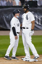 Chicago White Sox's Jose Abreu, right, is congratulated by third base coach Nick Capra after his three-run double during the fourth inning of a baseball game against the Chicago Cubs in Chicago, Saturday, Sept. 26, 2020. Abreu had advanced to third on an error on the play. (AP Photo/Nam Y. Huh)