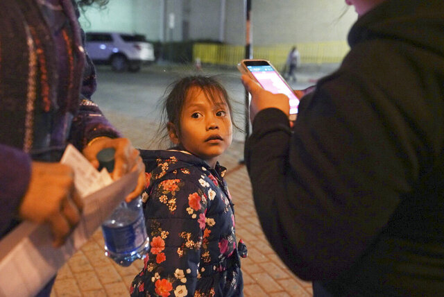 A 7-year-old asylum-seeker waits as her mother Isabel, right, and immigration lawyer Charlene D'Cruz, left, as they figure out where they will be spending the night after being processed at the Port of Entry in Brownsville, Texas, Tuesday, Dec. 17, 2019. The girl who is unable to contain her own waste due to a congenital illness and who had been refused entry to the United States three times has finally been allowed into the country. (AP Photo/Veronica G. Cardenas)