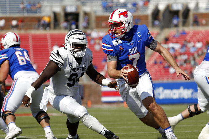 SMU quarterback Shane Buechele (7) scrambles out of the pocket while being chased by Memphis defensive lineman Joseph Dorceus (94) during the first half of an NCAA college football game in Dallas, Saturday, Oct. 3, 2020. (AP Photo/Roger Steinman)