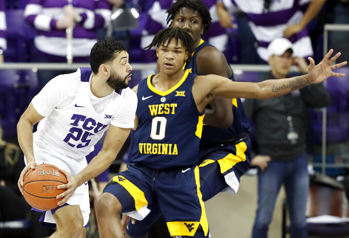 TCU guard Alex Robinson (25) looks for an opening against West Virginia guard Trey Doomes (0) in the first half of an NCAA college basketball game, Tuesday, Jan. 15, 2019, in Fort Worth, Texas. (AP Photo/Tony Gutierrez)