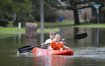 Josey Chambers, 11, and his brother Sawyer, 7, make they way on a kayak up Wandering Trail after Clear Creek overflowed as Tropical Storm Beta rained over the area Tuesday, Sept. 22, 2020, in Friendswood, Texas. (Steve Gonzales/Houston Chronicle via AP)