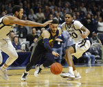 Marquette's Markus Howard (0) dribbles past Butler's Bryce Nze (10) and Henry Baddley (20) during the second half of an NCAA college basketball game, Friday, Jan. 24, 2020, in Indianapolis. Butler won, 89-85, in overtime. (AP Photo/Darron Cummings)
