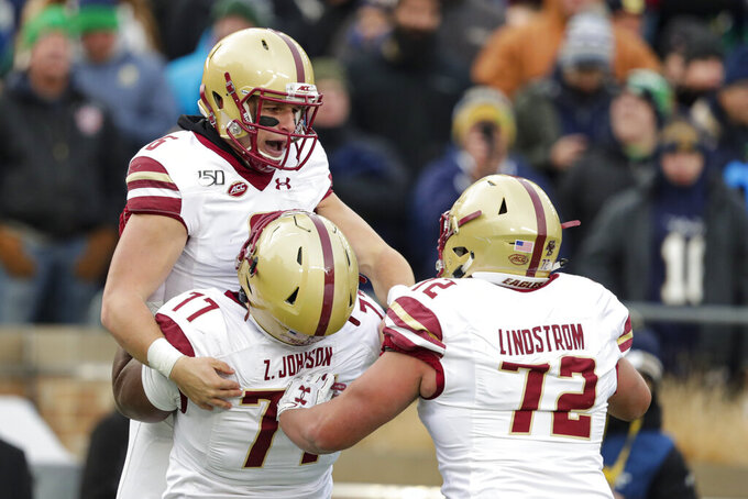 Boston College quarterback Dennis Grosel (6) celebrates his touchdown against Notre Dame with offensive lineman Zion Johnson (77) and Alec Lindstrom (72) during the first half of an NCAA college football game in South Bend, Ind., Saturday, Nov. 23, 2019. (AP Photo/Michael Conroy)