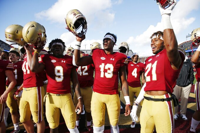 Boston College quarterback Anthony Brown (13), wide receiver Kobay White (9) and defensive back Lukas Denis (21) celebrate after defeating Louisville during an NCAA college football game in Boston, Saturday, Oct. 13, 2018. (AP Photo/Michael Dwyer)
