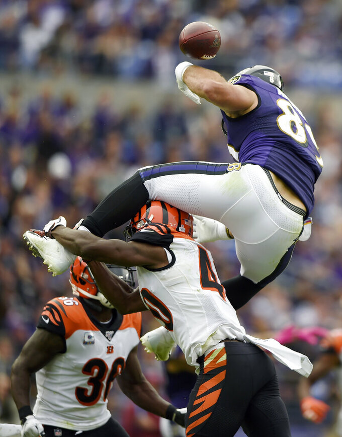 Baltimore Ravens tight end Mark Andrews, top, loses the ball while trying to leap over Cincinnati Bengals defensive back Brandon Wilson during the first half of a NFL football game Sunday, Oct. 13, 2019, in Baltimore. (AP Photo/Gail Burton)