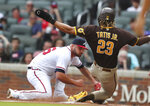 San Diego Padres' Fernando Tatis Jr. scores on a wild pitch past Atlanta Braves starting pitcher Bryse Wilson during the first inning in the second baseball game of a doubleheader Wednesday, July 21, 2021, in Atlanta. (Curtis Compton/Atlanta Journal-Constitution via AP)
