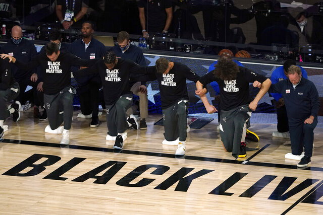 Members of the Milwaukee Bucks join arms as they kneel during the national anthem before an NBA basketball first round playoff game against the Orlando Magic Saturday, Aug. 29, 2020, in Lake Buena Vista, Fla. (AP Photo/Ashley Landis)
