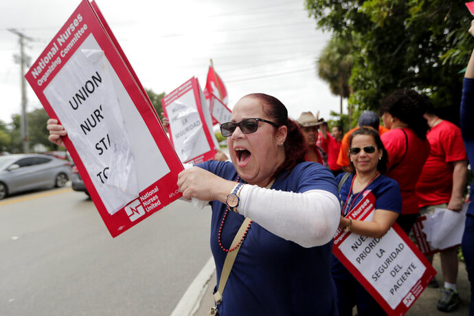 Nurse Cindy Rodriguez shouts during a one-day strike outside of Palmetto General Hospital, Friday, Sept. 20, 2019, in Hialeah, Fla. Registered nurses staged a one-day strike against Tenet Health hospitals in Florida, California and Arizona on Friday, demanding higher wages and better working conditions. (AP Photo/Lynne Sladky)