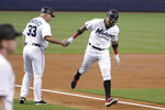 Miami Marlins' Starlin Castro, right, shakes hands with third base coach Fredi Gonzalez (33) after hitting a solo home run during the first inning of a baseball game against the Kansas City Royals, Sunday, Sept. 8, 2019, in Miami. (AP Photo/Lynne Sladky)