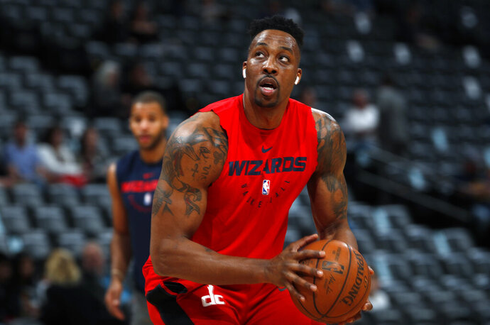 FILE - In this March 31, 2019, file photo, injured Washington Wizards center Dwight Howard practices before the Wizards face the Denver Nuggets in an NBA basketball game in Denver. A person familiar with the decision says the Los Angeles Lakers intend to sign Howard after he completes a buyout with Memphis. The person spoke on condition of anonymity Friday, Aug. 23, 2019, because the deal has not been completed for Howard to make an improbable return to the Lakers six years after his acrimonious departure. Howard played in only nine games last season for Washington, which traded him to the Grizzlies last month. (AP Photo/David Zalubowski, File)