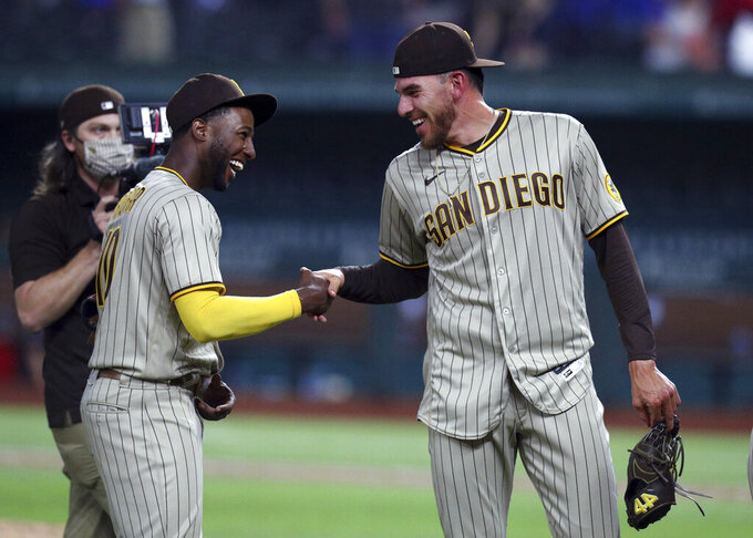 San Diego Padres' Jurickson Profar, left, shakes hands with pitcher Joe Musgrove (44) after Musgrove's no-hitter against the Texas Rangers during a baseball game Friday, April 9, 2021, in Arlington, Texas. (AP Photo/Richard W. Rodriguez)