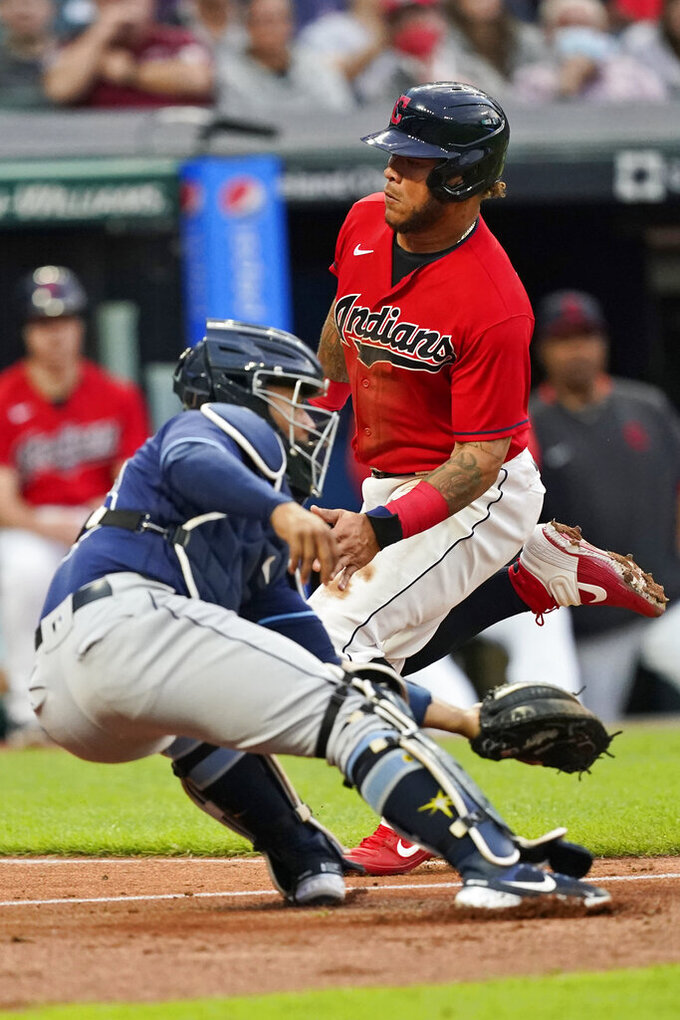 Cleveland Indians' Harold Ramirez, right, scores as Tampa Bay Rays catcher Francisco Mejia is late on the tag during the fourth inning of a baseball game Thursday, July 22, 2021, in Cleveland. (AP Photo/Tony Dejak)