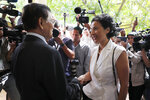 Cambodia National Rescue Party's President Kem Sokha, front left, shakes hands with French Ambassador to Cambodia Eva Nguyen Binh, front right, before a meeting at his house in Phnom Penh, Cambodia, Monday, Nov. 11, 2019. A Cambodian court has lifted some restrictions on detained opposition leader Kem Sokha, essentially ending his house arrest. (AP Photo/Heng Sinith)