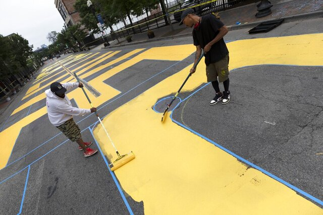 Lee Beard, left, and Mar, no last name given, paint the phrase Black Lives Matter on Washington Street, Sunday, July 5, 2020, in the Roxbury neighborhood of Boston. (AP Photo/Michael Dwyer)