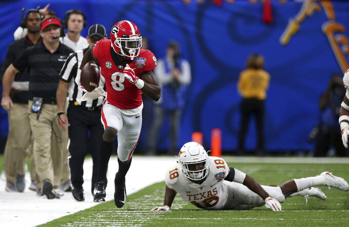 Georgia wide receiver Riley Ridley (8) runs past Texas defensive back Davante Davis (18) in the first half of the Sugar Bowl NCAA college football game in New Orleans, Tuesday, Jan. 1, 2019. (AP Photo/Rusty Costanza)