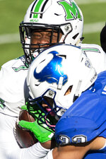 Marshall wide receiver Corey Gammage (7) is tackled by Buffalo safety Tyrone Hill (33) during the Camellia Bowl NCAA college football game in Montgomery, Ala., Friday, Dec. 25, 2020. (Jake Crandall/The Montgomery Advertiser via AP)