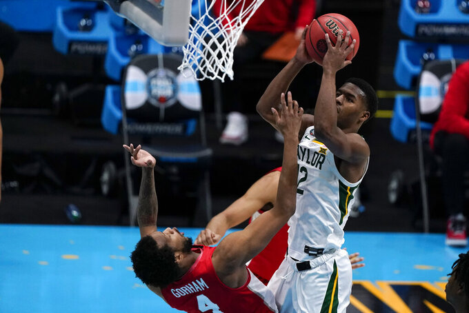 Baylor guard Jared Butler (12) shoots over Houston forward Justin Gorham, left, during the first half of a men's Final Four NCAA college basketball tournament semifinal game, Saturday, April 3, 2021, at Lucas Oil Stadium in Indianapolis. (AP Photo/Michael Conroy)