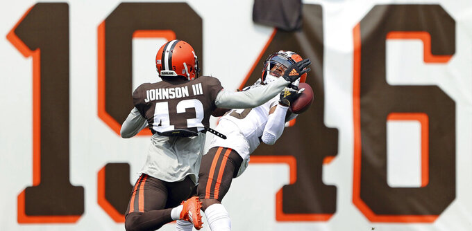 Cleveland Browns running back Demetric Felton tries to catch a pass over his shoulder as strong safety John Johnson defends during an Orange and Brown NFL football practice in Cleveland, Sunday, Aug. 8, 2021. (Joshua Gunter/The Plain Dealer via AP)