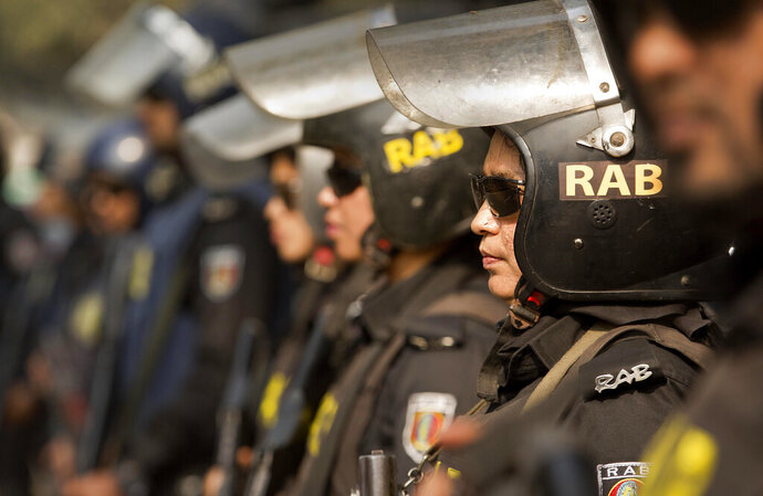 "FILE- A Dec. 29, 2018 file photo of Bangladesh police's elite Rapid Action Battalion (RAB), a security force focused on combating extremist groups, in Dhaka, Bangladesh. Indian and Bangladeshi officials and security experts largely dismissed a fresh threat of violence from an Islamic State-aligned media group, insisting that routine monitoring of would-be militants would prevent a Sri Lanka-style attack from taking place elsewhere in South Asia. Al-Mursalat Media released a graphic on Tuesday of five militants who carried out a 2016 attack at a cafe in the diplomatic enclave of Bangladesh's capital, Dhaka, according to global terrorism monitor SITE Intelligence. Mufti Mahmud Khan, a spokesman for RAB, told The Associated Press that he didn't place ""any great emphasis"" on the threat released by the IS-aligned media group. (AP Photo/Anupam Nath, File)"