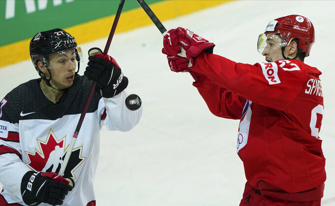 Artyom Shvets-Rogovoi of Russia, right, fight for a puck with Michael Bunting of Canada during the Ice Hockey World Championship quarterfinal match between Russia and Canada at the Olympic Sports Center in Riga, Latvia, Thursday, June 3, 2021. (AP Photo/Roman Koksarov)
