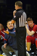 Arizona head coach Sean Miller, left, gestures while talking to an official during the second half of his team's NCAA college basketball game against Stanford in Santa Cruz, Calif., Saturday, Dec. 19, 2020. (AP Photo/Jeff Chiu)