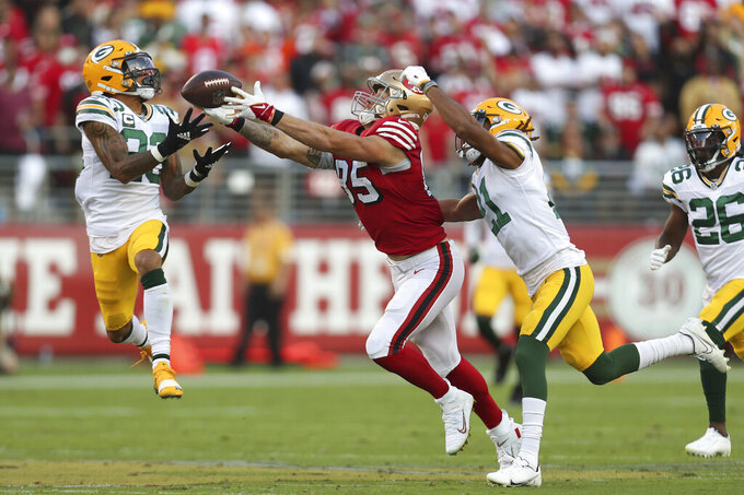 Green Bay Packers cornerback Jaire Alexander, left, intercepts a pass intended for San Francisco 49ers tight end George Kittle, middle, during the first half of an NFL football game in Santa Clara, Calif., Sunday, Sept. 26, 2021. (AP Photo/Jed Jacobsohn)