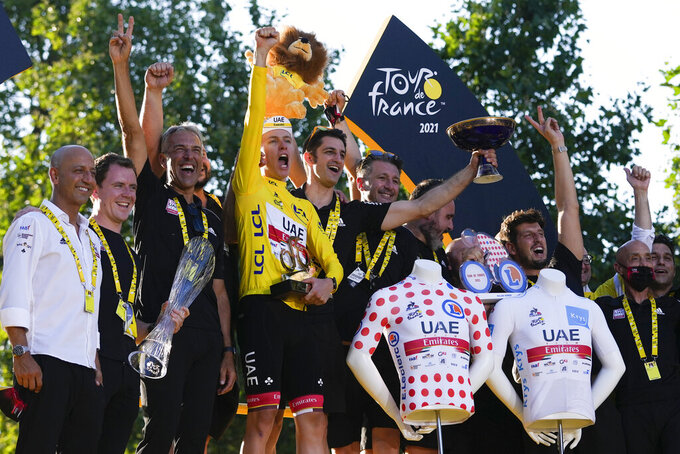 Tour de France winner Slovenia's Tadej Pogacar, who won the overall leader's yellow jersey, the best climber's dotted jersey, and the best young rider's white jersey, celebrates with his team after the twenty-first and last stage of the Tour de France cycling race over 108.4 kilometers (67.4 miles) with start in Chatou and finish on the Champs Elysees in Paris, France,Sunday, July 18, 2021. (AP Photo/Daniel Cole)