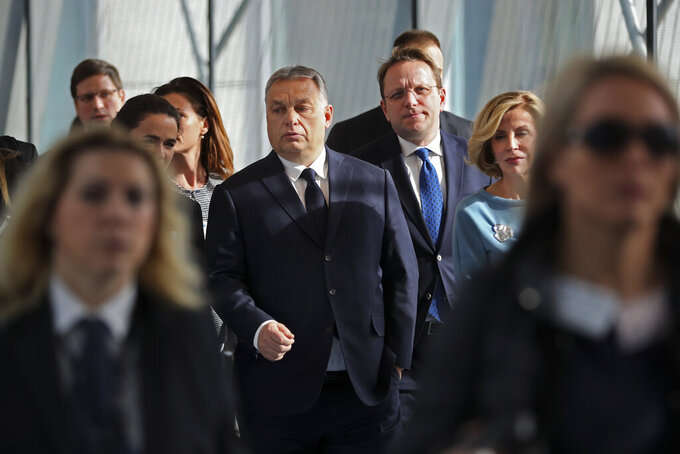 FILE - In this Wednesday, March 20, 2019 file photo, Hungarian Prime Minister Viktor Orban, center, arrives to a European People's Party's meeting at the European Parliament in Brussels. Hungary's governing party pulled out of its conservative group in the European Union's legislature on Wednesday, March 3, 2021, following years of conflict over the rule of law and European values. In a letter Wednesday to Manfred Weber, chairman of the EPP Group in the European Parliament, Hungarian Prime Minister Viktor Orban announced Fidesz's decision to leave the group. (AP Photo/Francisco Seco, File)