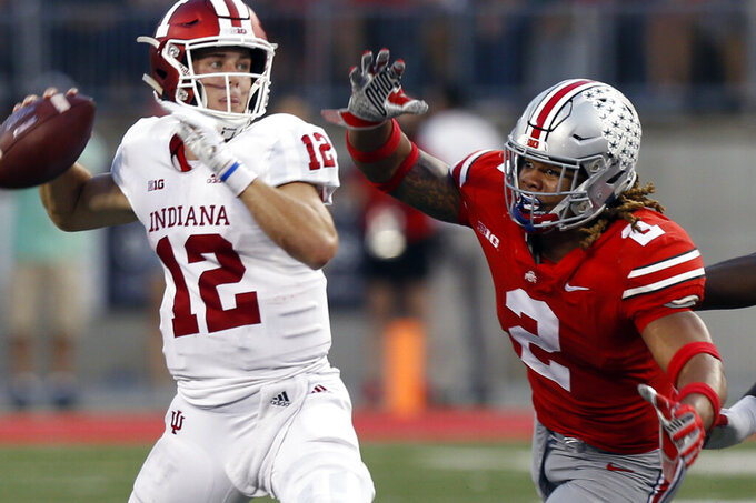 FILE - In this Oct. 6, 2018, file photo, Indiana quarterback Peyton Ramsey, left, throws a pass just before being hit by Ohio State defensive end Chase Young during the second half of an NCAA college football game in Columbus, Ohio. Chase Young is known to lead with his mouth. Being the loudest Buckeye on the field is part of the reason his teammates elected him a captain this season. The other part is that he can back it up the chattering. Young is Ohio State's best player, a 6-foot-5, 265-pound man with startling quickness and a mean streak who rarely stops cheering, cajoling and trash-talking. (AP Photo/Jay LaPrete, File)