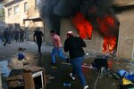 FILE - In this Oct. 17, 2020 file photo, the headquarters of Kurdish Democratic Party burn during a protest by pro-Iranian militiamen and their supporters in Baghdad, Iraq. Iran-aligned Shiite militias are posing an increasing challenge for Iraq ahead of key talks with Washington in early April 2021, that are meant to shape the future of the U.S.-Iraq relationship. (AP Photo/Khalid Mohammed, File)