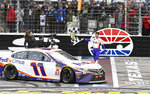 Driver Denny Hamlin celebrates with the checkered flag after winning a NASCAR Cup auto race at Texas Motor Speedway, Sunday, March 31, 2019, in Fort Worth, Texas. (AP Photo/Larry Papke)