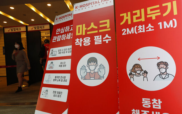 A woman wearing a face mask walks near banners showing precautions against the coronavirus at an exhibition hall of K-Hospital Fair in Seoul, South Korea, Wednesday, Oct. 21, 2020. (AP Photo/Lee Jin-man)