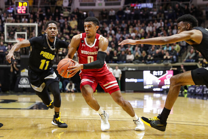 Wisconsin guard D'Mitrik Trice (0) cuts between Purdue guard Isaiah Thompson (11) and forward Aaron Wheeler (1) during the first half of an NCAA college basketball game in West Lafayette, Ind., Friday, Jan. 24, 2020. (AP Photo/Michael Conroy)