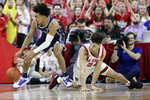 Duke guard Tre Jones, left, reaches for a loose ball while North Carolina State guard Devon Daniels (24) defends during the first half of an NCAA college basketball game in Raleigh, N.C., Wednesday, Feb. 19, 2020. (AP Photo/Gerry Broome)