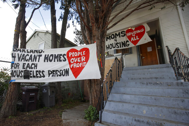 FILE - In this Jan. 14, 2020, file photo, signs are posted outside of a house that was occupied by the group Moms 4 Housing in Oakland, Calif. Homeless moms evicted from a San Francisco Bay Area house they occupied illegally earlier this year now own the home and plan to turn it into housing for other people experiencing homelessness. Moms 4 Housing said Friday, Oct. 9, 2020, they have signed the deed to the dilapidated West Oakland home, which now belongs to the Oakland Community Land Trust. (AP Photo/Jeff Chiu, File)