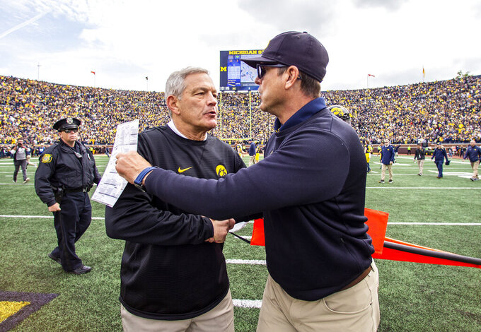 Iowa head coach Kirk Ferentz, left, shakes hands with Michigan head coach Jim Harbaugh, right, after an NCAA college football game in Ann Arbor, Mich., Saturday, Oct. 5, 2019. Michigan won 10-3. (AP Photo/Tony Ding)
