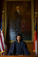 """FILE - In this Feb. 13, 2019, file photo, Cheri Beasley poses for a portrait in the court room from the Chief Justice's seat in Fayetteville, N.C.   In North Carolina's Supreme Court chamber, above the seat held by Beasley, the second African American chief justice, hangs a towering painting of Chief Justice Thomas Ruffin, a 19th century slave owner and jurist who authored a notorious opinion about the """"absolute"""" rights of slaveholders over the enslaved.In October 2018 the state Supreme Court named a commission to review the portraits in the building that houses the court,including Ruffin's.(Melissa Sue Gerrits/The Fayetteville Observer via AP, File)"""