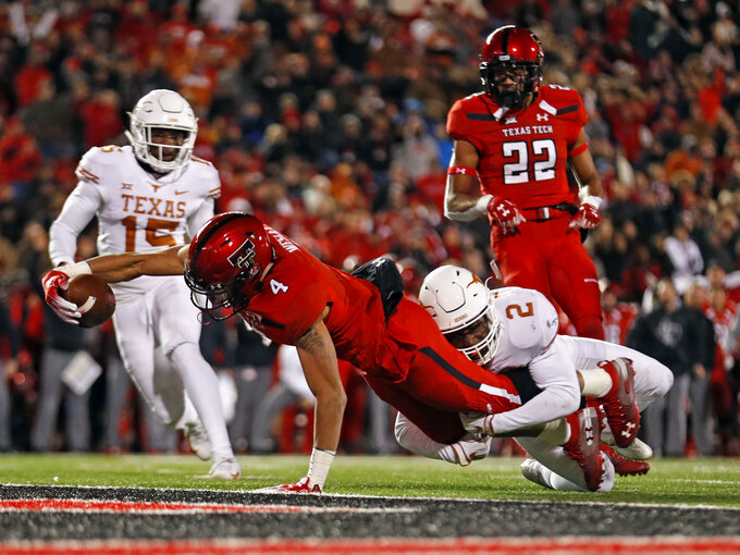 Texas Tech's Antoine Wesley (4) stretches across the goal line to score a touchdown as Texas' Kris Boyd (2) defends during the second half of an NCAA college football game Saturday, Nov. 10, 2018, in Lubbock, Texas. (AP Photo/Brad Tollefson)