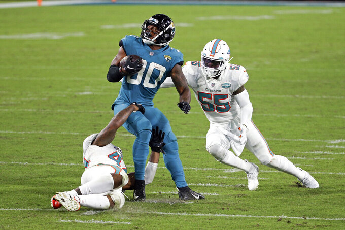 Jacksonville Jaguars running back James Robinson, center, looks for a way to get past Miami Dolphins outside linebacker Elandon Roberts, left, and outside linebacker Jerome Baker (55) during the second half of an NFL football game, Thursday, Sept. 24, 2020, in Jacksonville, Fla. (AP Photo/Stephen B. Morton)