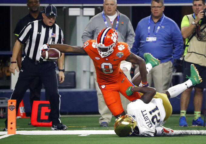 Clemson wide receiver Justyn Ross (8) leans forward and reaches the end zone for a touchdown after getting past Notre Dame safety Jalen Elliott (21) in the first half of the NCAA Cotton Bowl semi-final playoff football game, Saturday, Dec. 29, 2018, in Arlington, Texas. (AP Photo/Roger Steinman)