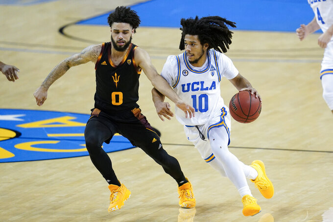 Arizona State guard Holland Woods (0) defends against UCLA guard Tyger Campbell (10) during the second half of an NCAA college basketball game Saturday, Feb. 20, 2021, in Los Angeles. (AP Photo/Ashley Landis)
