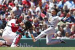 Seattle Mariners' J.P Crawford, right, scores on a double by Daniel Vogelbach as Boston Red Sox's Sandy Leon fields the throw during the first inning of a baseball game in Boston, Saturday, May 11, 2019. (AP Photo/Michael Dwyer)