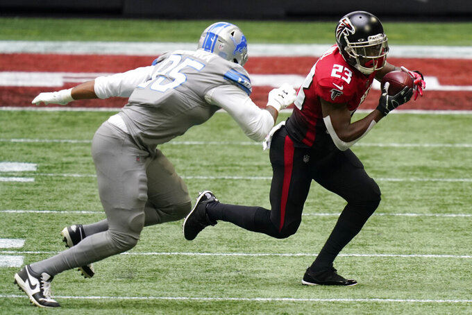 Atlanta Falcons running back Brian Hill (23) runs past Detroit Lions defensive end Romeo Okwara (95) during the first half of an NFL football game, Sunday, Oct. 25, 2020, in Atlanta. (AP Photo/Brynn Anderson)